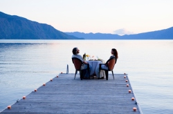 Caucasian couple having dinner on pier at lake